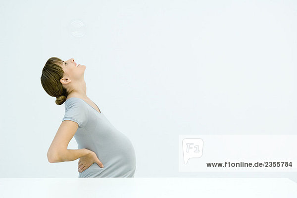 Pregnant woman looking up at bubble  hands on hips  side view