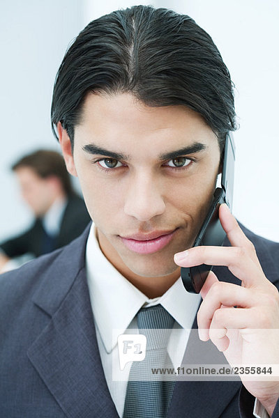 Young businessman using cellphone  smiling at camera  portrait