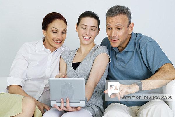 Teenagerin  die mit ihren Eltern tragbare DVD-Player anschaut  alle lächelnd