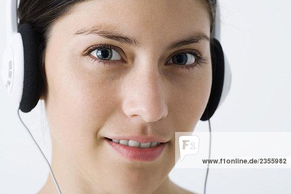 Junge Frau hört Kopfhörer  schaut in die Kamera  Nahaufnahme