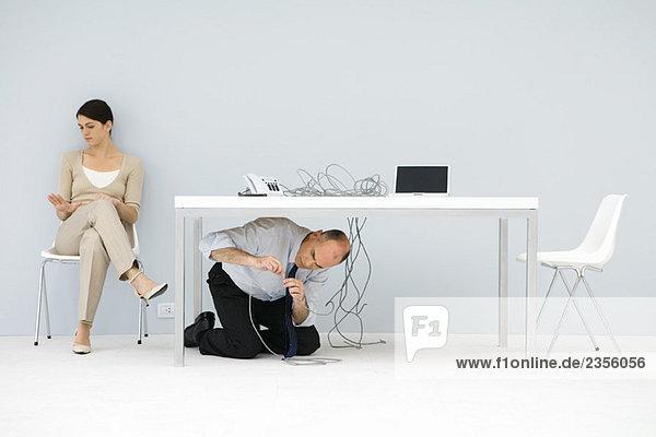 Mann kniend unter dem Schreibtisch  verwirrte Drähte verbindend  Frau im Stuhl sitzend  auf die Hand schauend