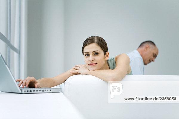 Frau lehnt sich über den Rücken der Couch  benutzt den Laptop  lächelt in die Kamera.