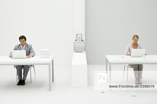 Kollegen im Büro mit Laptop-Computern  Drucker zwischen ihnen mit Dokumentengrafik  Papierkugeln auf dem Boden verstreut