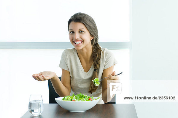 Teen girl eating salad  holding up hand and shrugging shoulders