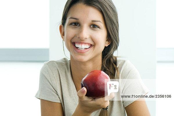 Teen Mädchen hält bis Apple  Lächeln in die Kamera  Portrait Teen Mädchen hält bis Apple, Lächeln in die Kamera, Portrait