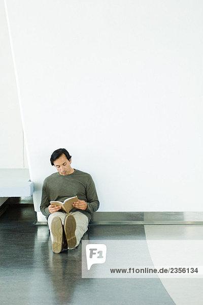 Man sitzt auf Boden  Lesebuch  voller Länge Man sitzt auf Boden, Lesebuch, voller Länge
