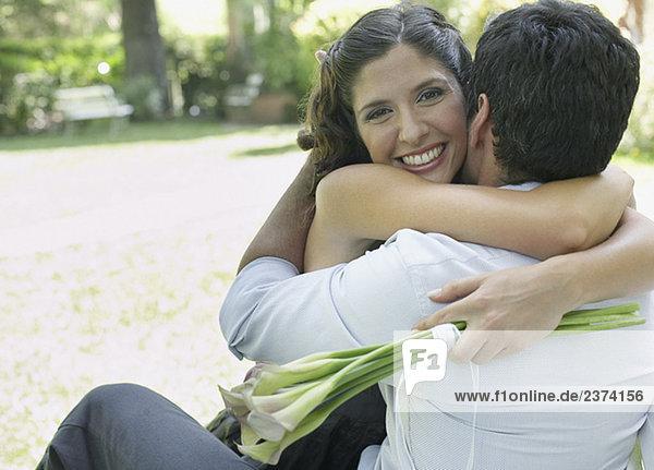 Paar umarmen mit Blumen lächelnd Außenaufnahme