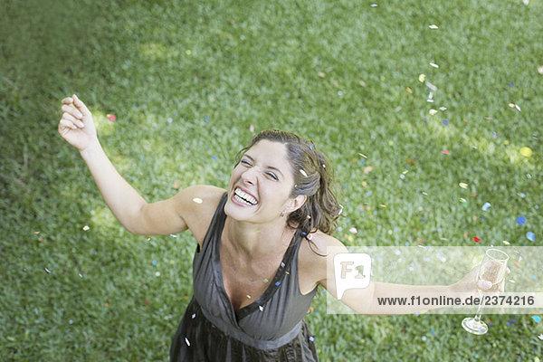 Außenaufnahme stehend Frau lächeln Konfetti Gras Champagner freie Natur