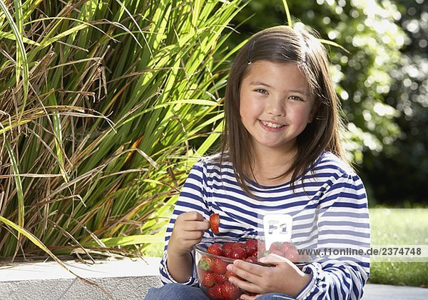 Young girl sitting outdoors with a bowl of strawberries smiling