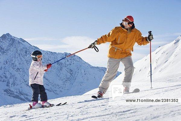 Mutter zieht Kind auf Skiern