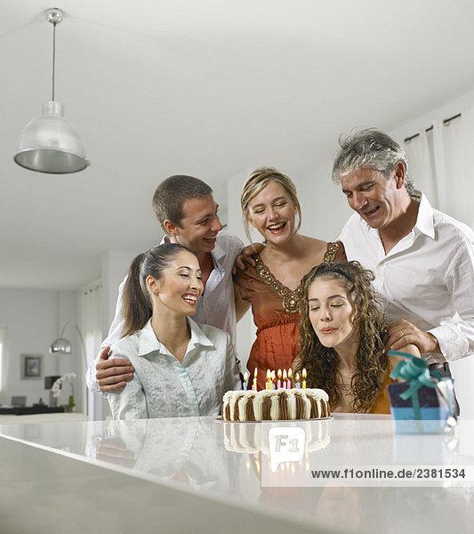 Familie sitzt um einen Geburtstagskuchen herum
