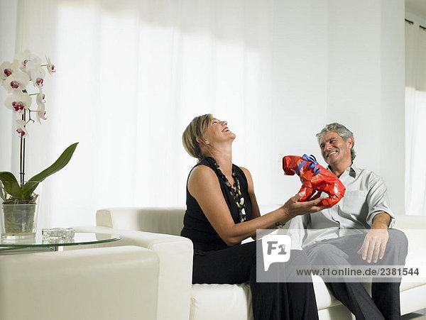 Eine Frau  die über ein Geschenk lacht.