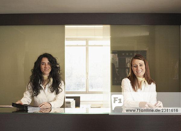 Zwei Rezeptionisten hinter dem Hotelschalter