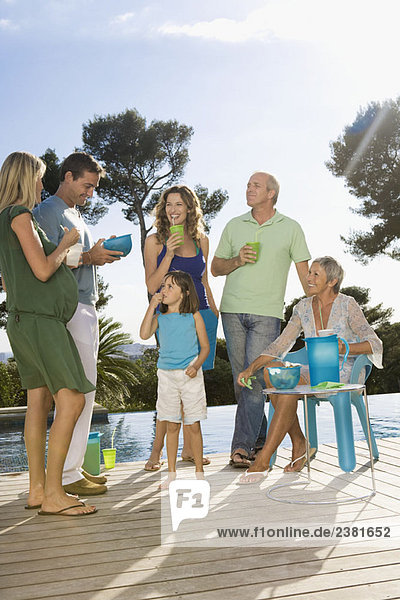 Family on a wooden terrace by a pool