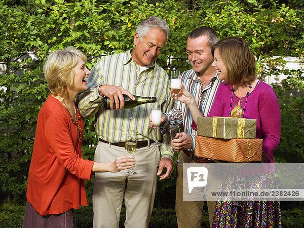 Senior Mann gießt Champagner für Freunde.