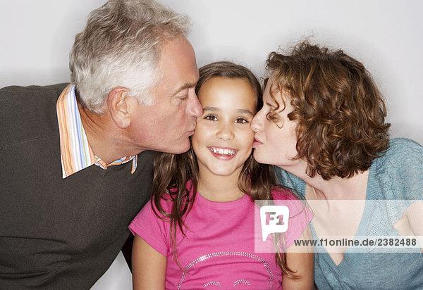 Opa und Mama küssen die Wange des Mädchens.