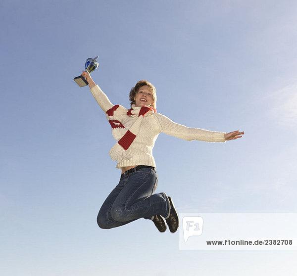 Frau springt  hält Trophäe