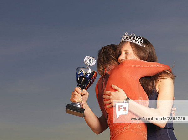Frau umarmt Frau  hält Trophäe