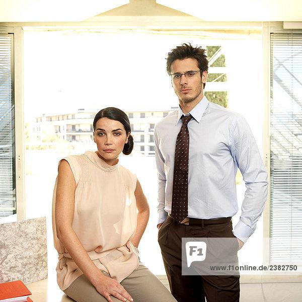 Paar im Büro mit Blick auf die Kamera