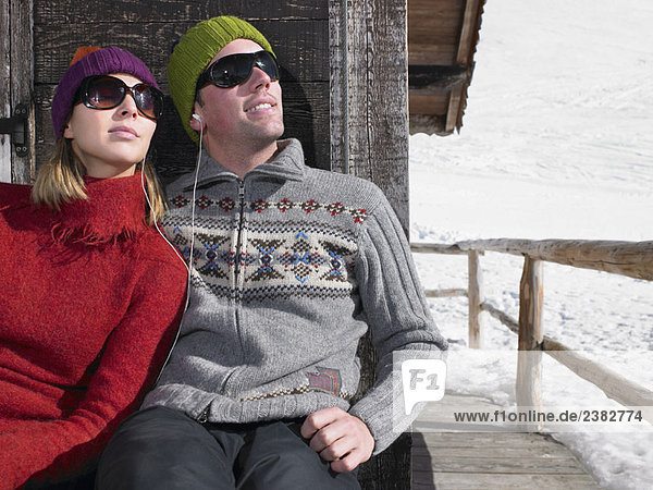 Paar hört Musik im Chalet