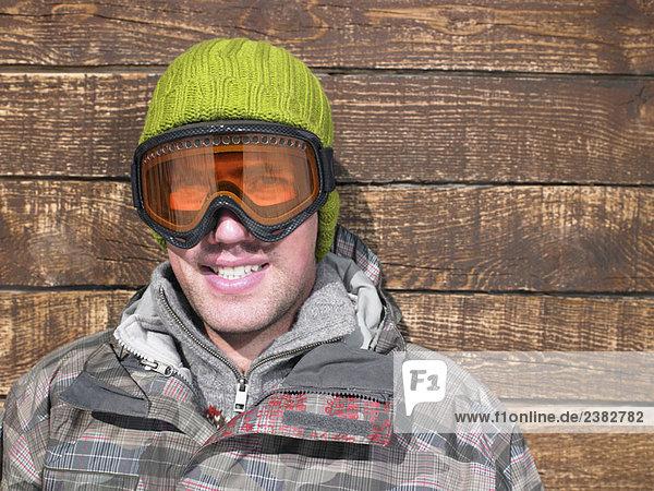 Junger Mann mit Brille und Schneekleidung
