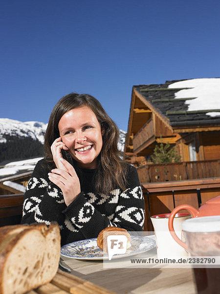 Junge Frau am Telefon beim Frühstück