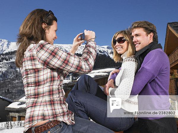 Junge Frau beim Fotografieren eines Paares