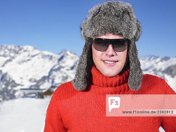 Junger Mann mit Hut in den Bergen