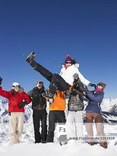 Gruppe wirft junge Frau in die Luft