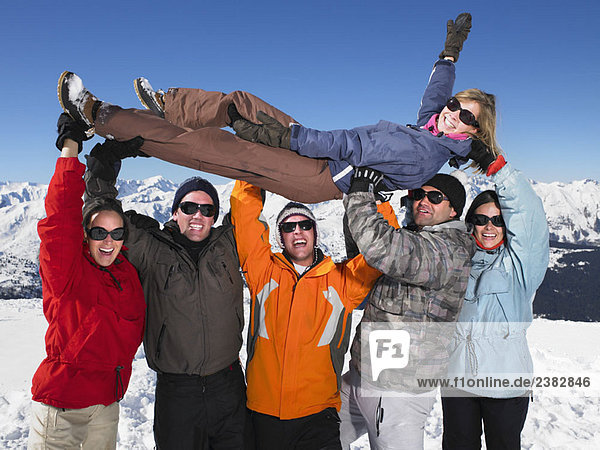 Gruppe hält junge Frau in der Luft