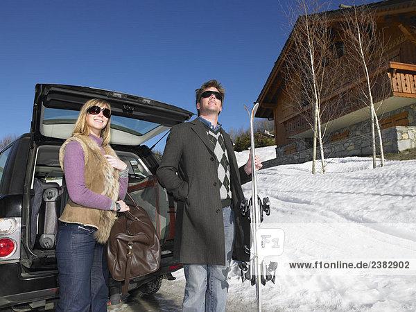 Junger Mann und Frau vor dem Auto