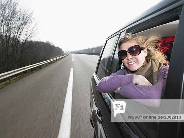 Junge Frau  die sich aus dem Autofenster lehnt.
