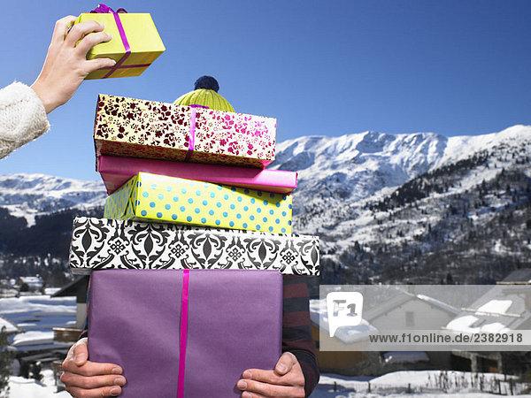 Junger Mann mit vielen Geschenken