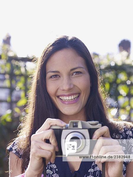 Junge Frau lächelt und hält Kamera