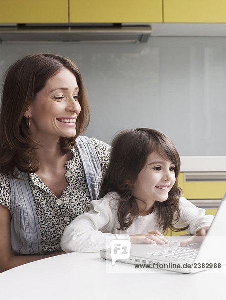 Mutter und junges Mädchen mit Laptop