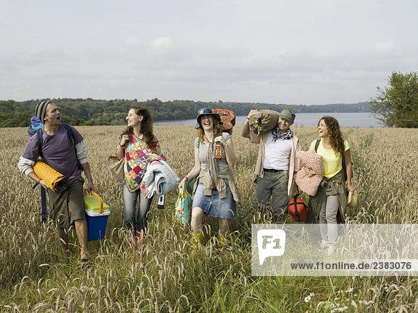 Five people walking together in field