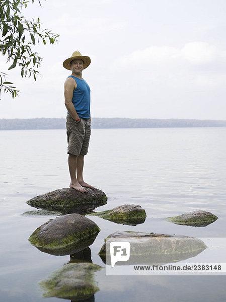 Mann steht auf Stein im Wasser