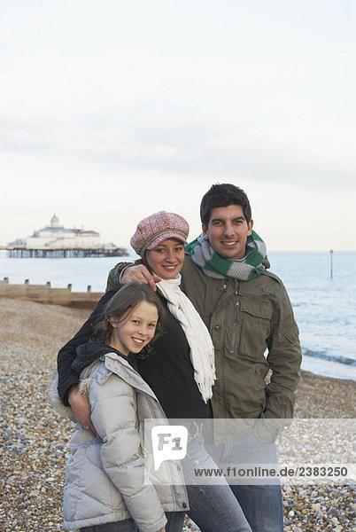 Glückliches Paar und Mädchen am Strand