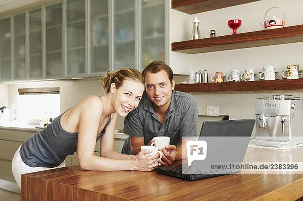 Paar lächelt in der Küche vor der Kamera