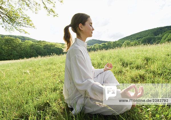 Frau sitzt im Gras und meditiert