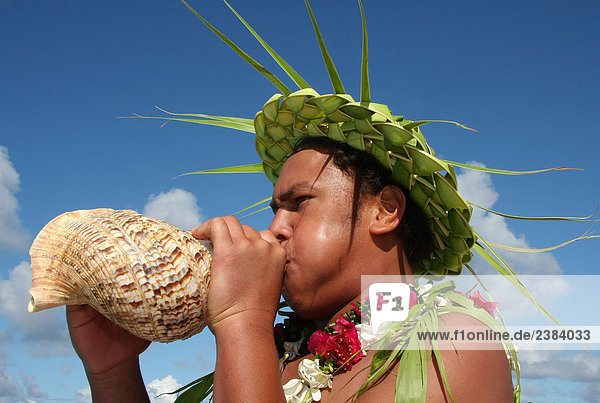 Close-up of man blowing sea shell, Makemo, Tuamotu Archipelago, French Polynesia, Polynesia, Pacific Island