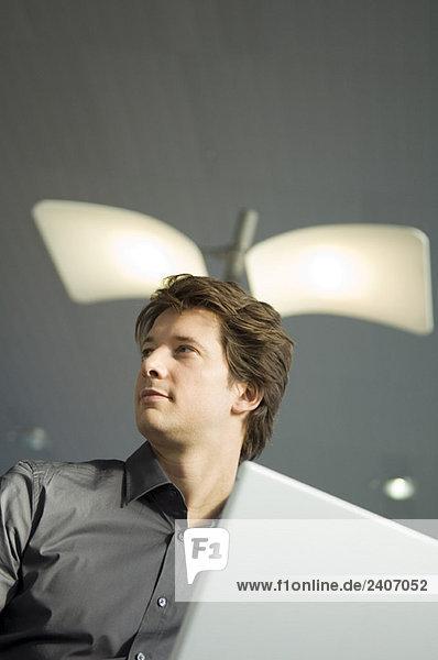 Niederwinkelansicht eines Geschäftsmannes bei der Arbeit am Laptop Niederwinkelansicht eines Geschäftsmannes bei der Arbeit am Laptop