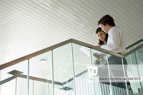 Niederwinkelansicht eines Geschäftsmannes und einer Geschäftsfrau beim Betrachten einer Blaupause Niederwinkelansicht eines Geschäftsmannes und einer Geschäftsfrau beim Betrachten einer Blaupause