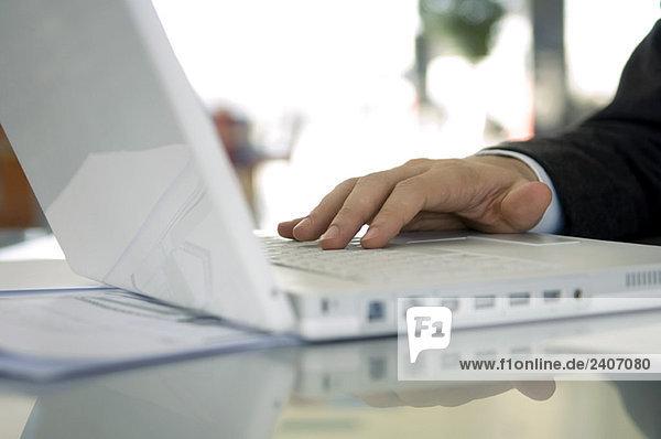 Nahaufnahme der Hand eines Geschäftsmannes mit einem Laptop