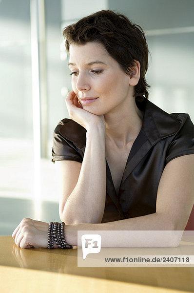 Nahaufnahme einer mittleren erwachsenen Frau am Tisch mit der Hand am Kinn