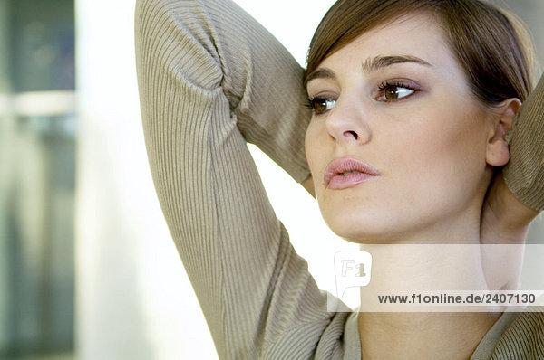 Nahaufnahme einer jungen Frau mit den Händen hinter dem Kopf Nahaufnahme einer jungen Frau mit den Händen hinter dem Kopf