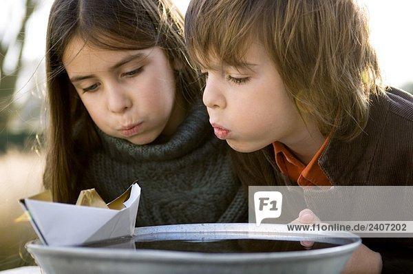 Nahaufnahme von zwei Kindern  die das Papierboot auf einer Schüssel mit Wasser blasen.