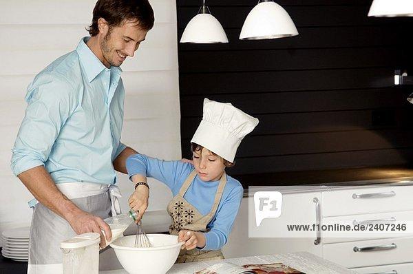 Ein erwachsener Mann  der mit seinem Sohn in der Küche einen Kuchen backt.