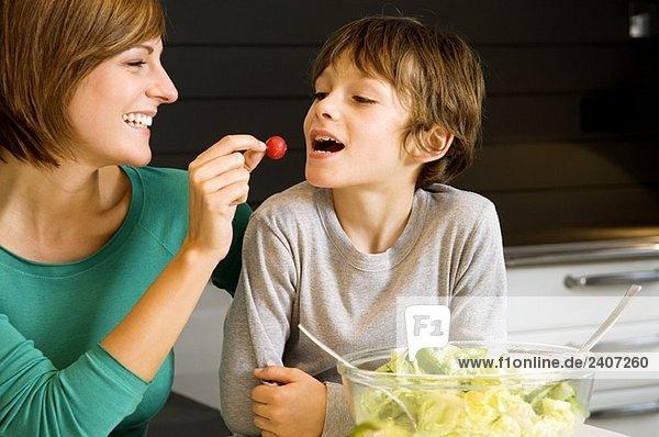 Junge Frau füttert ihren Sohn mit Rettich Junge Frau füttert ihren Sohn mit Rettich