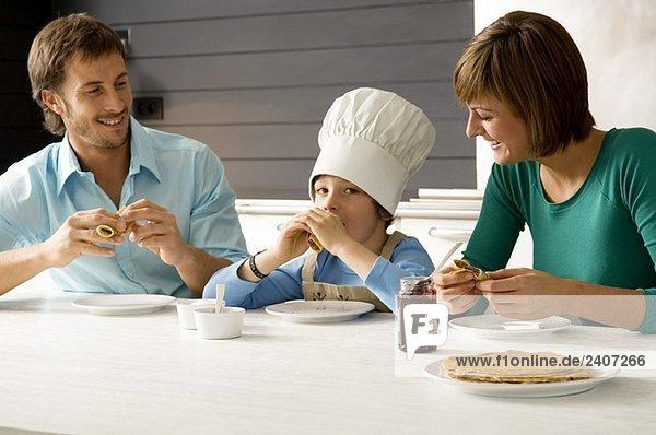 Ein erwachsener Mann und eine junge Frau beim Frühstück mit ihrem Sohn.